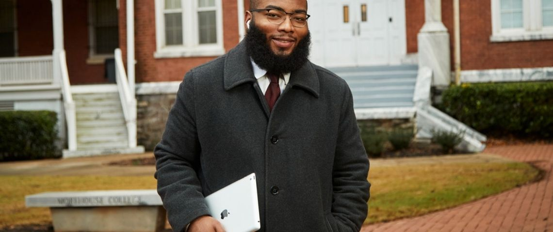 Un homme noir tient une tablette apple dans les mains