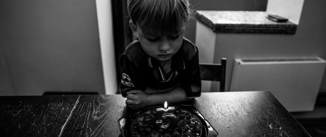 Photo en noir et blanc, d'un enfant assis seule, devant un gateau, avec une bougie pour ses 5 ans