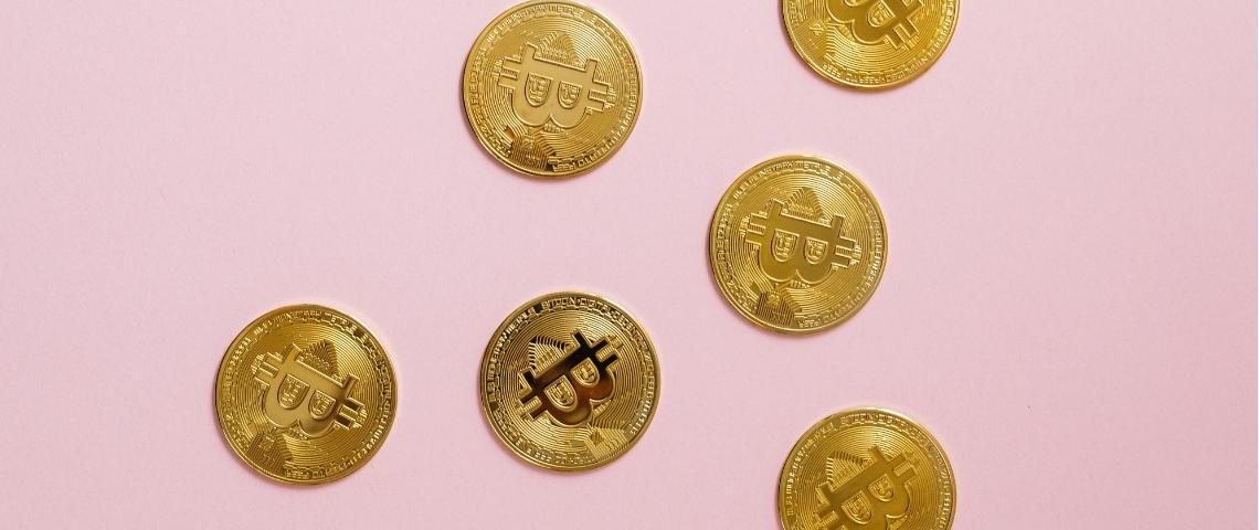 Des bitcoins sur un fond rose