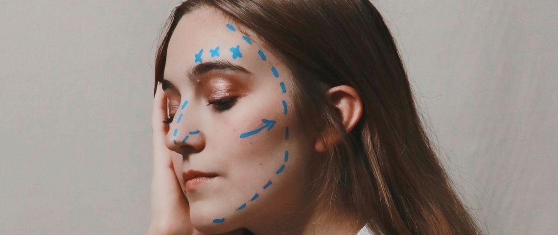 Une femme avec du crayon sur le visage comme avant une opération chirurgicale
