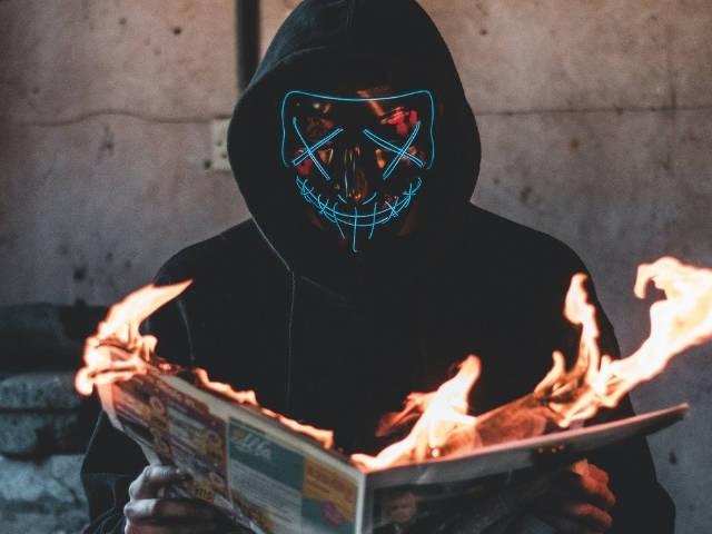 Un homme masqué en train de lire un journal en feu