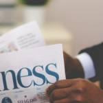 Jeune homme lisant un journal business