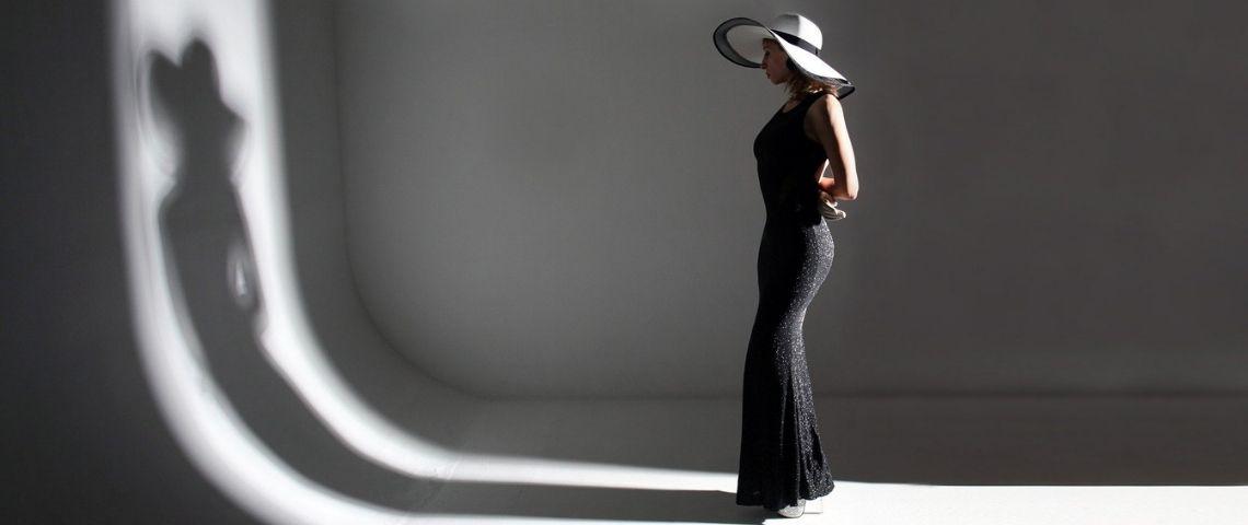 Jeune femme habillée avec une robe haute couture, regardant son reflet dans un mur