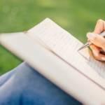 jeune femme écrivant sur un cahier