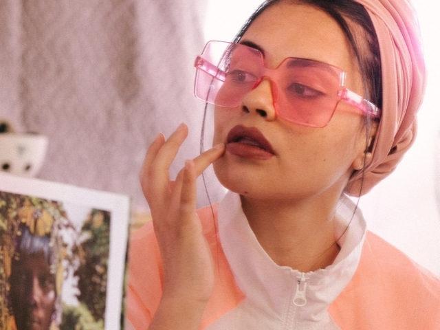 Une femme en train de se maquiller devant un miroir, portant un turban et des lunettes roses