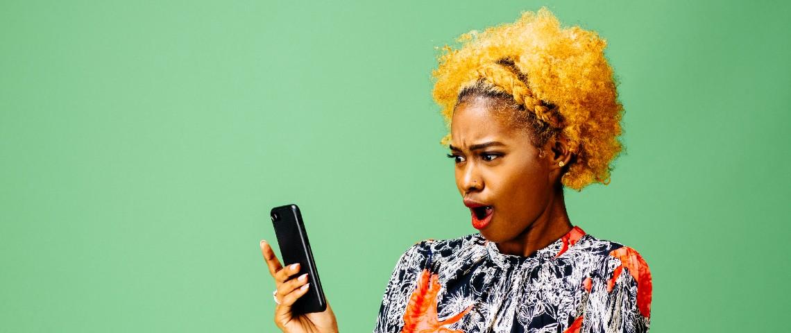 Une femme s'offusque devant son smartphone