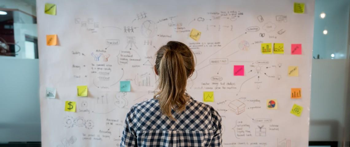 Une femme devant un tableau recouvert de post-it et de notes