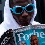 Jeune homme en train de lire un numéro du magazine Forbes
