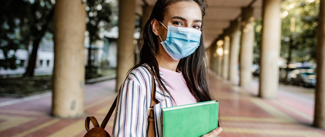Une jeune femme portant un masque dans les couloirs d'une université