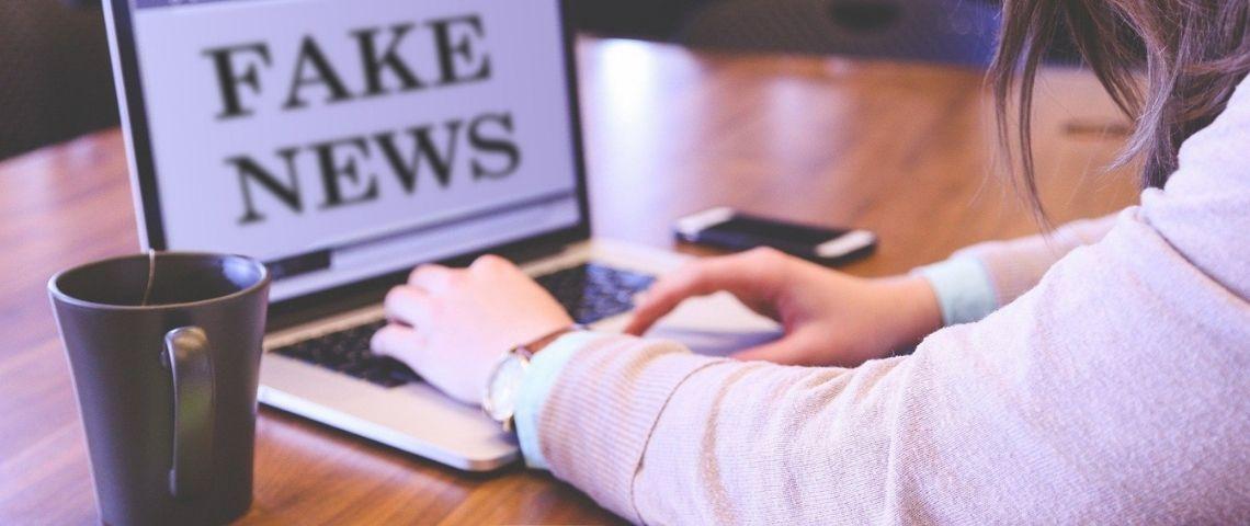 Jeune femme devant un ordinateur où il y a écrit  - Fake News -