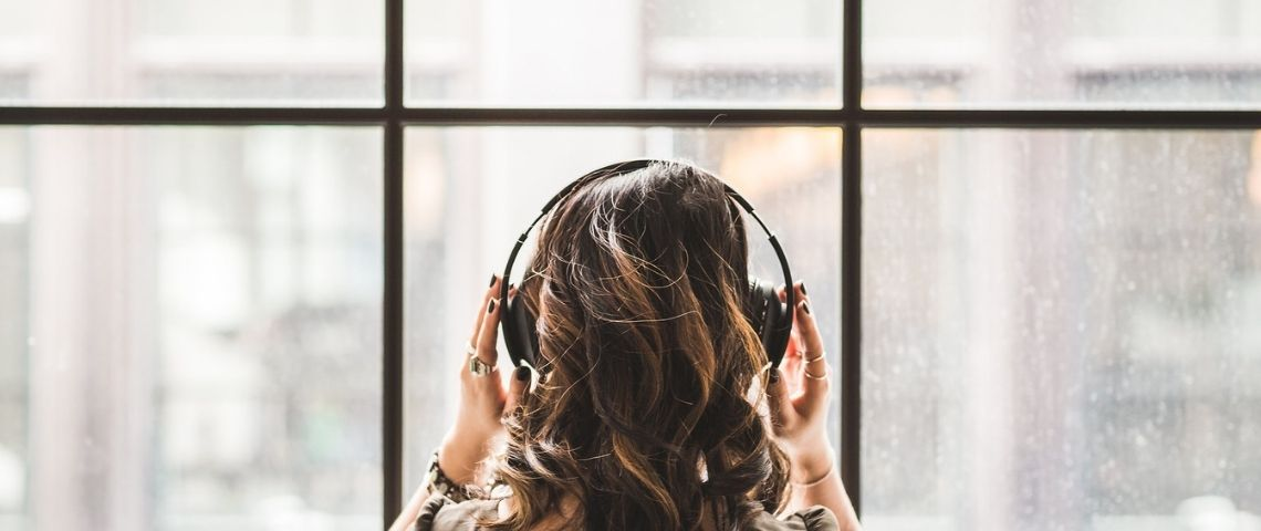 Femme de dos avec un casque sur les oreilles
