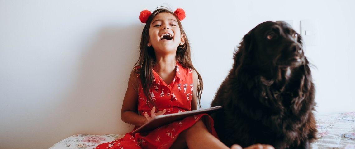 Petite riant avec une tablette dans les mains, assise sur son lit, accompagnée de son chien