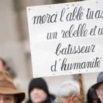 Pancarte : Merci l'abbé tu as été un rebelle et un batisseur d'humanité