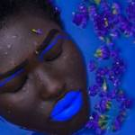 Une femme avec des lèvres bleues dans une baignoire remplie de liquide bleu