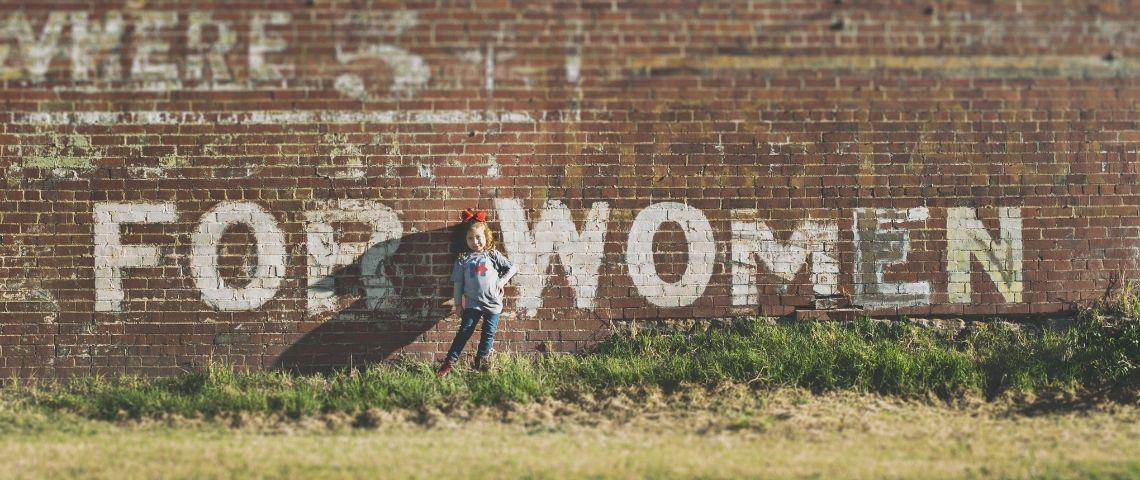 Petite fille devant un mur de briques rouges sur lequel est inscrit  - Women -