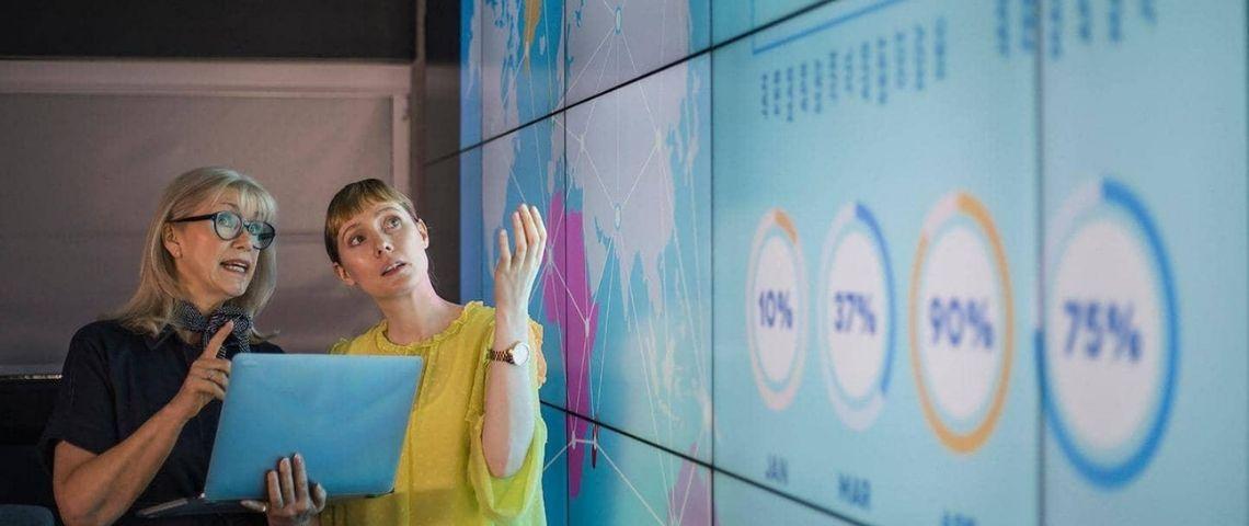 2 femmes devant des écrans remplis de chiffres