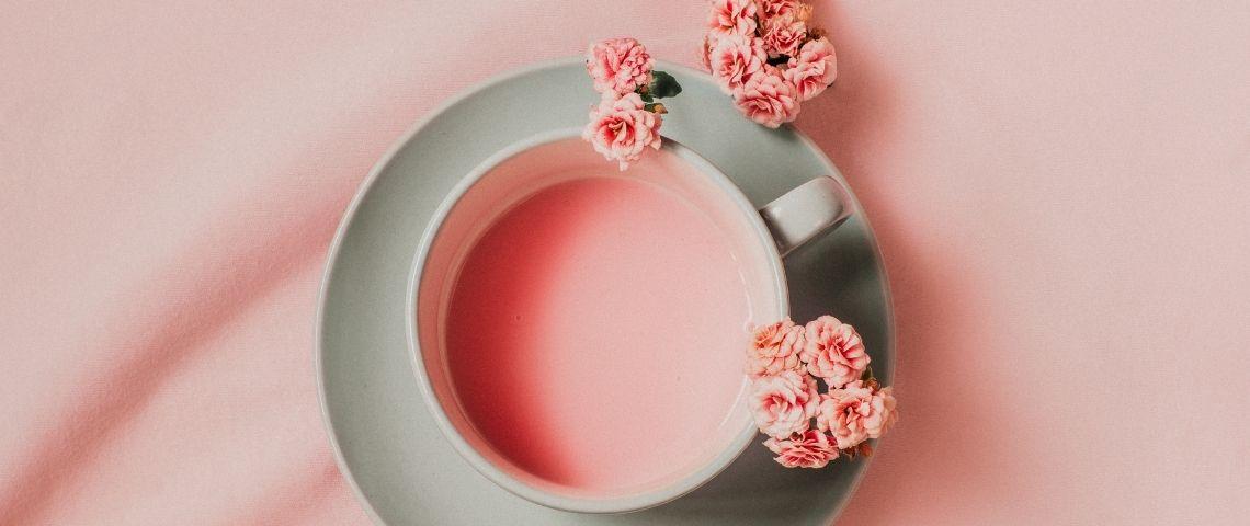 Une tasse avec un liquide rose et des fleurs roses
