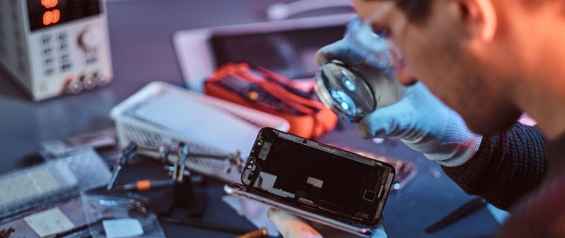 Un homme répare un smartphone