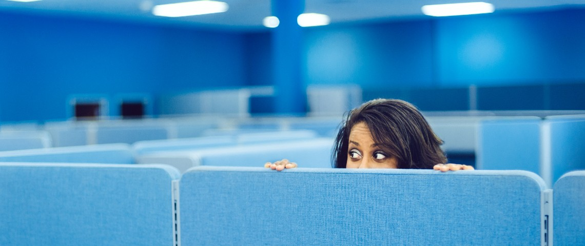 Une femme se cache derrière une paroi dans un grand open-space