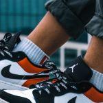 Un garçon porte une paire de Nike, buildings en fond