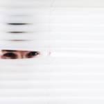 Une personne qui regarde derrière un rideau