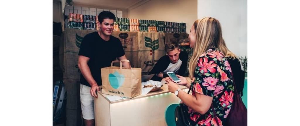 Jeune femme récupérant un sac de nourriture portant le logo Too Good To Go dans un restaurant