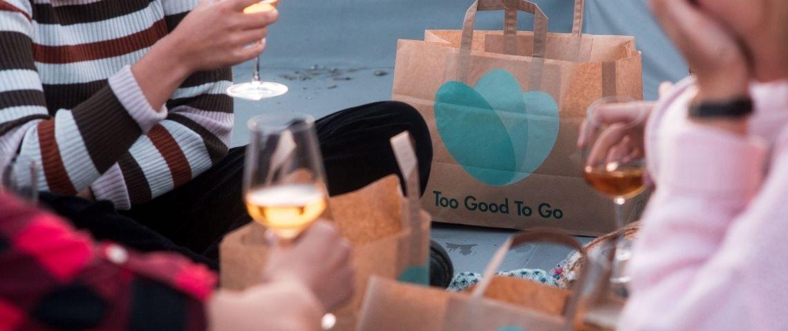 Personne partageant un déjeuner, avec des sacs au logo de Too Good To Go