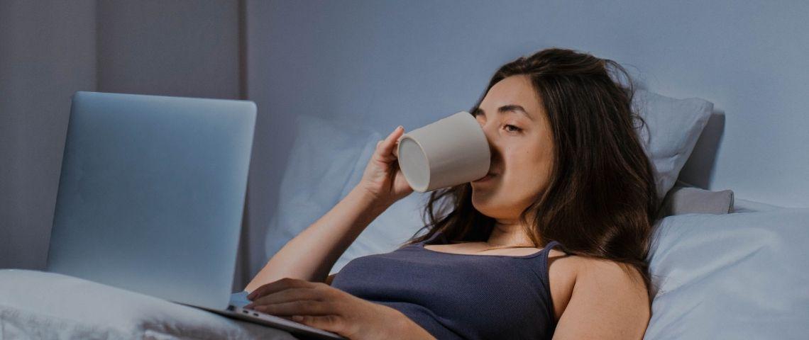 Une femme en pyjama dans son lit devant son ordinateur portable en train de boire une tasse de café