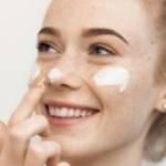 Une femme se met de la crème sur le visage