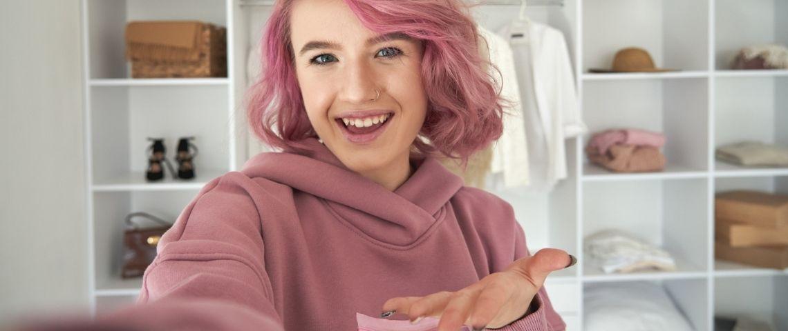 Une adolescente avec les cheveux roses en train de faire du live shopping