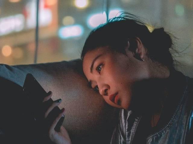 Jeunes fille devant son écran de téléphone portable, avec un air triste
