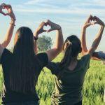 Jeunes filles de dos faisaint des coeurs avec leurs mains