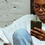 Une jeune femme noire en train de regarder son téléphone alors qu'elle mange
