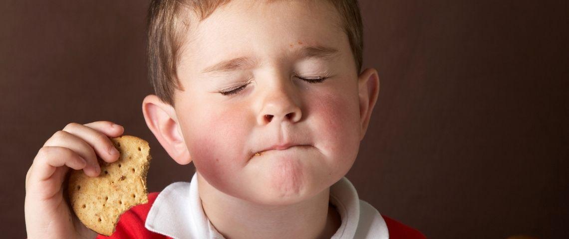 Un petit garçon qui mange un gâteau en fermant les yeux