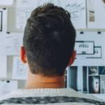 Jeune homme réfléchissant face à un tableau plein de données