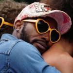 Homme noir avec des lunettes en forme de coeur, serrant dans es bras un homme blanc