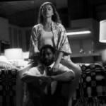 Femme assise au bord du lit, avec un homme devant, assis au sol