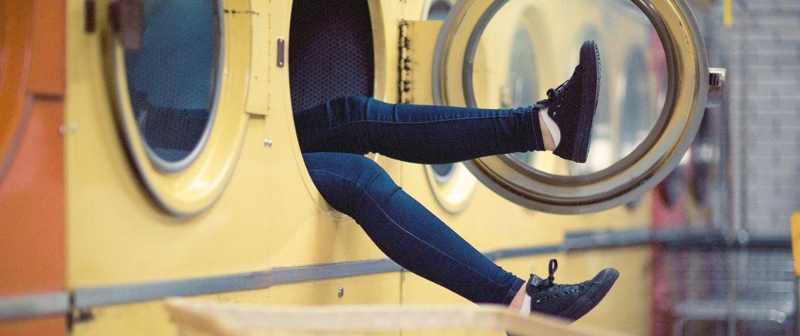 Jeune femme assise dans une machine à laver, laissant dépasser ses 2 jambes