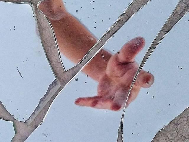 Une main dans un miroir cassé