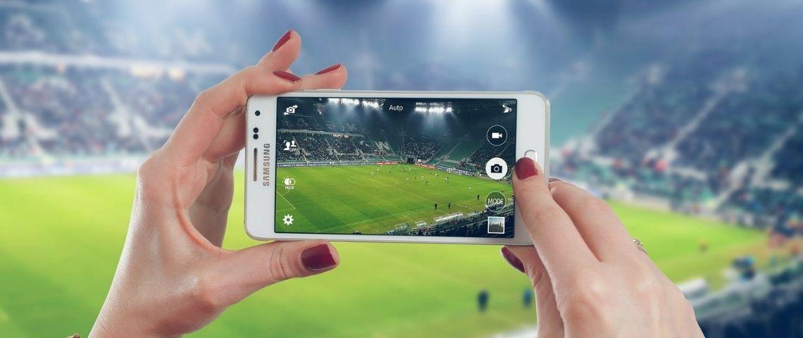 Personne filmant un match de foot avec son téléphone portable