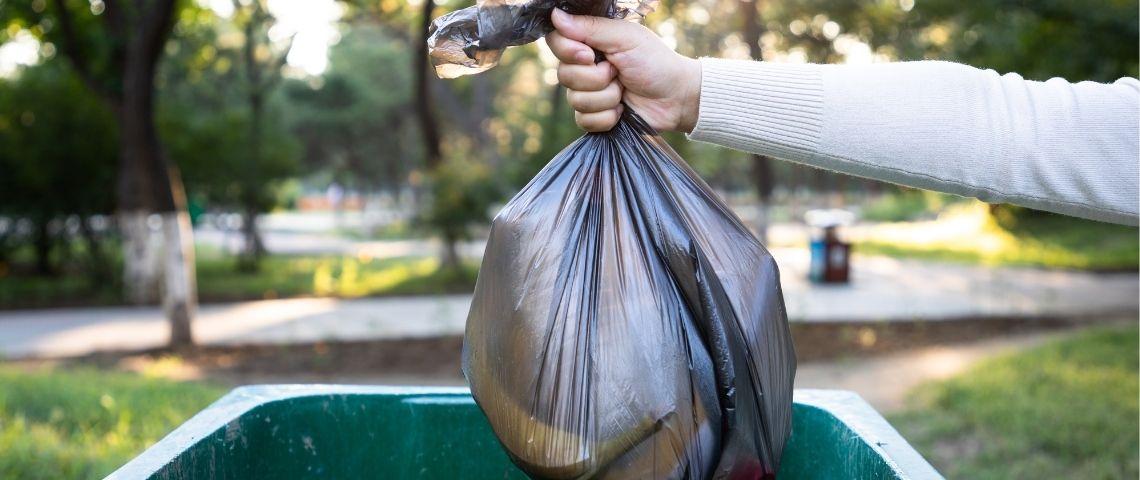 Personne jetant un sac dans une poubelle