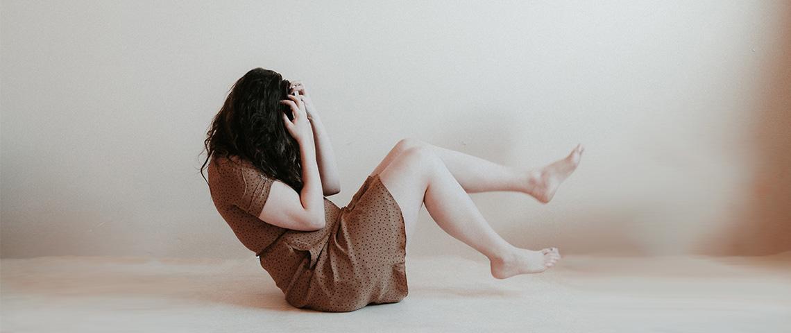 femme de profil, au sol, se prenant la tête entre les mains