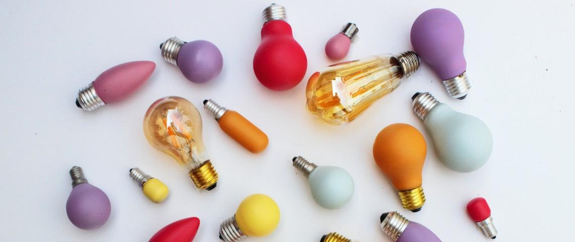 Des ampoules de différentes couleurs éparpillées sur un fond blanc