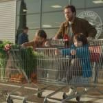 Papa sortant d'un supermaché Intermarché, avec 2 caddies, dans lesquels se trouvent un enfant qui fait mine de conduire une voiture