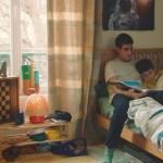 Deux frères sur un lit, le grand racontant une histoire au plus petit