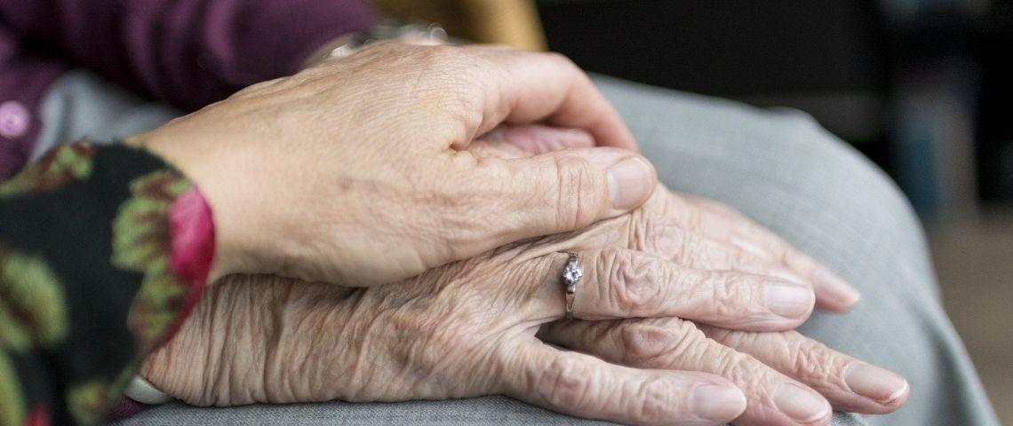 2 mains de personnes âgées, l'un sur l'autre