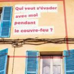 """Femme à sa fenêtre, avec le message suivant inscrit sur le mur de son immeuble : """"Qui veut s'écvader avec moi pendant le couvre-feu ?"""""""