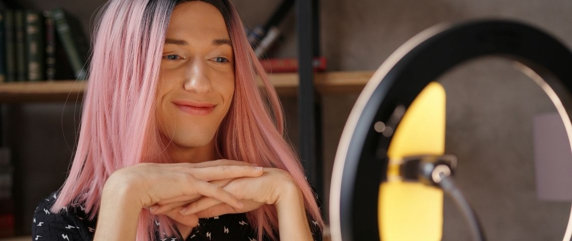 Une femme avec des cheveux roses devant une ring light TikTok