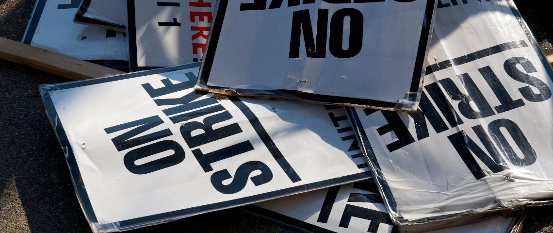 Des panneaux  - on strike -  entassés sur le bitume