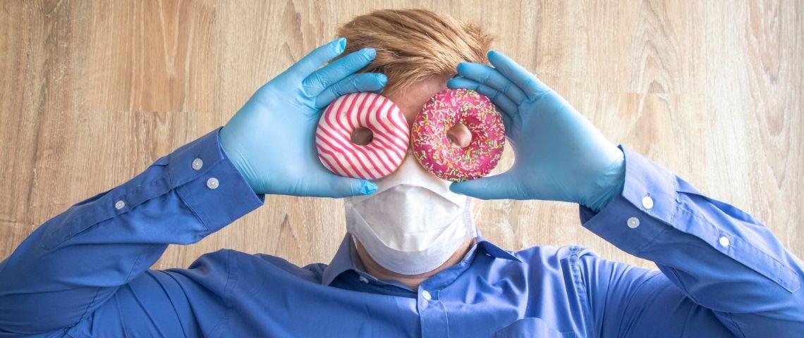 Un homme masqué et ganté tenant deux donuts devant ses yeux
